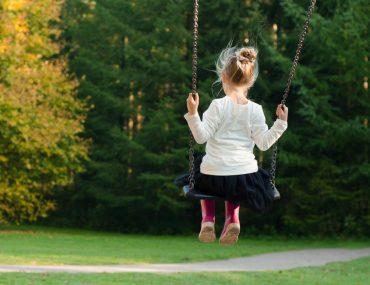 giocare all'aria aperta bambina altalena
